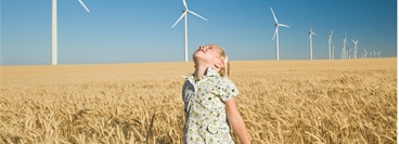Girl stood in field in front of wind farm